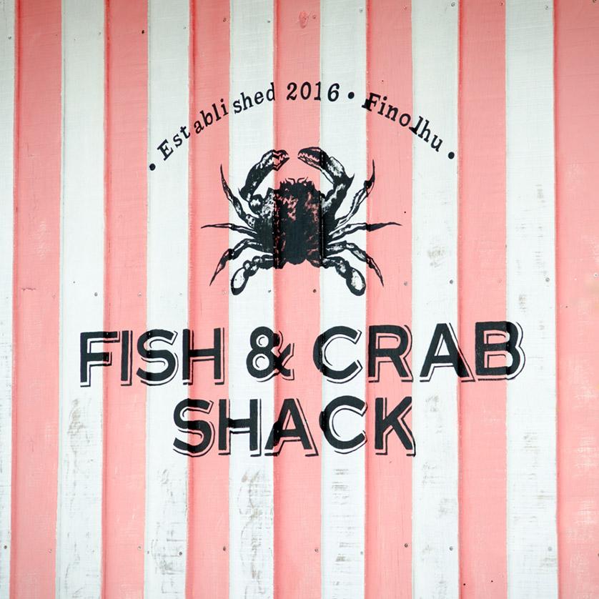 Logo des Crab Shack Restaurants auf Holzfassade gemalt