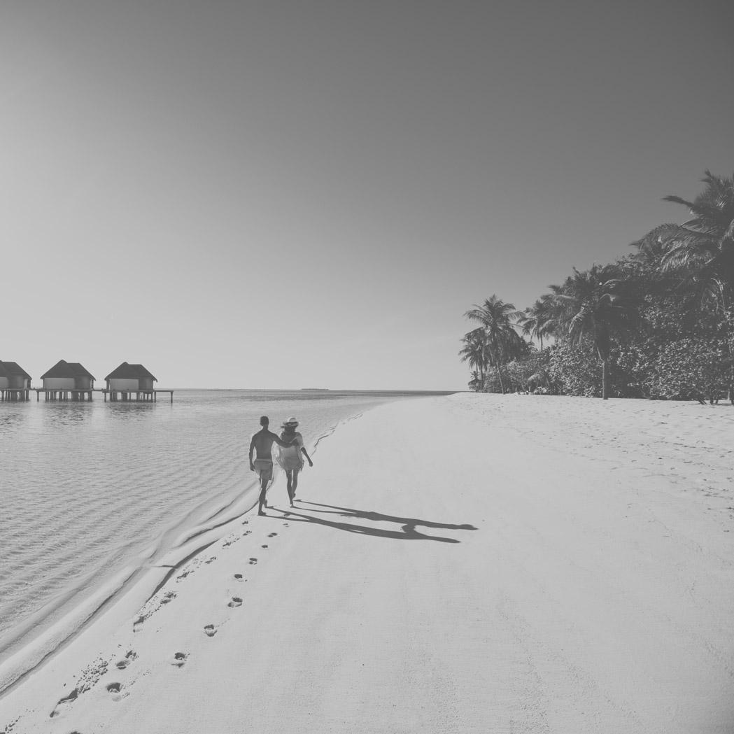 Paar spaziert über Sandstrand im Kanuhura