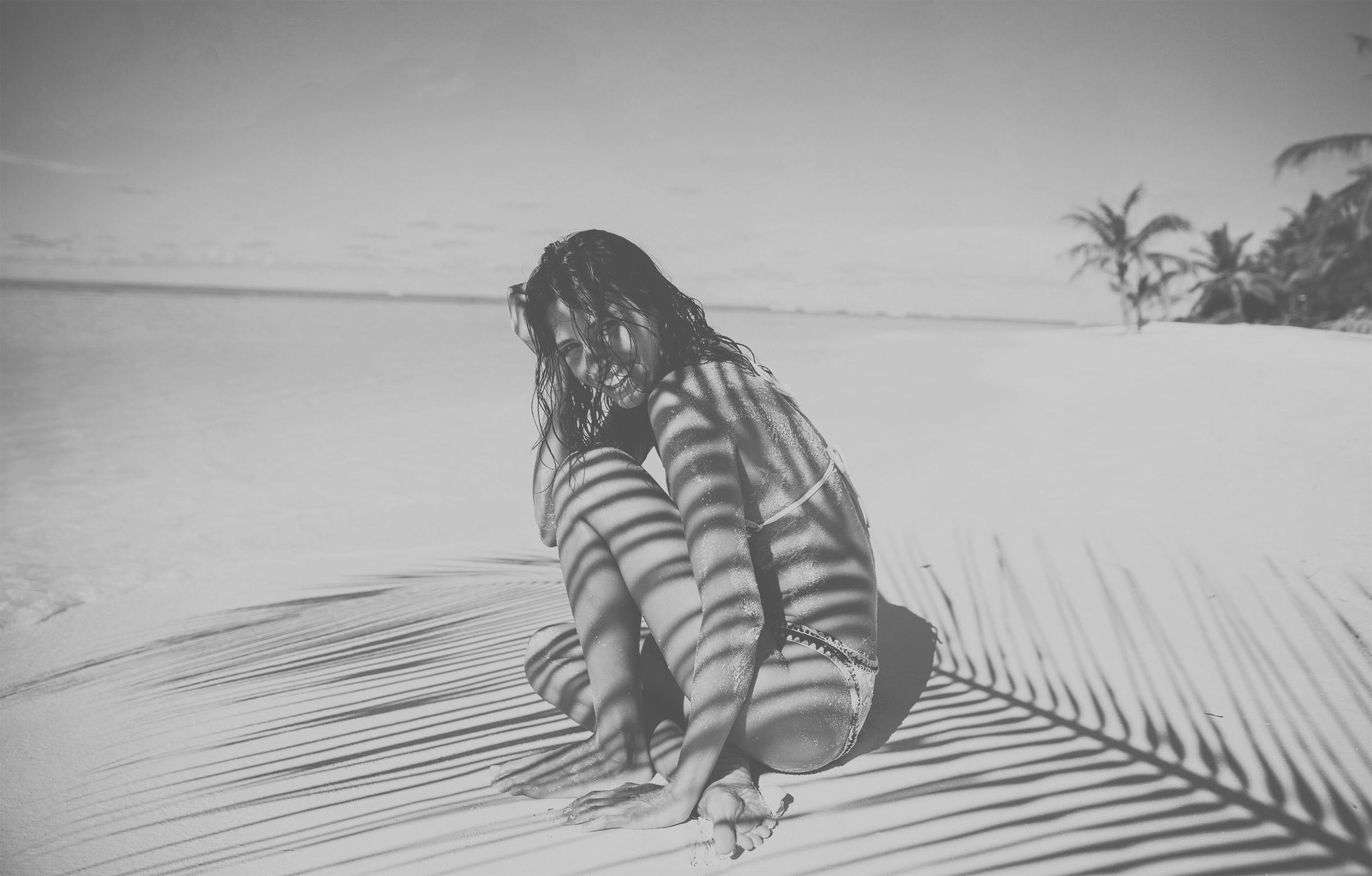 Frau sitzt im Schatten einer Palme am Strand des Kanuhura