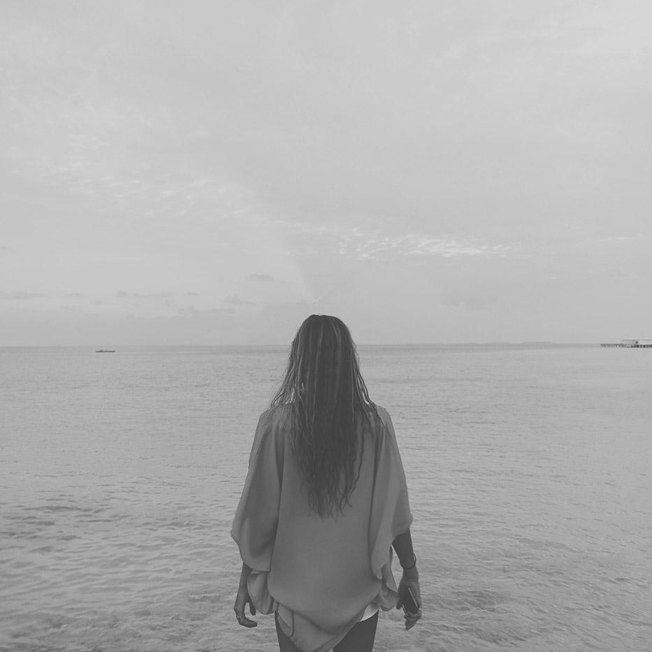 Frau steht an Malediven-Strand und Blickt über das Meer