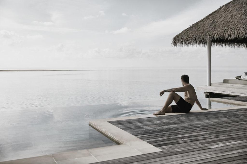 Man sitzt am Pool in einer Water Villa