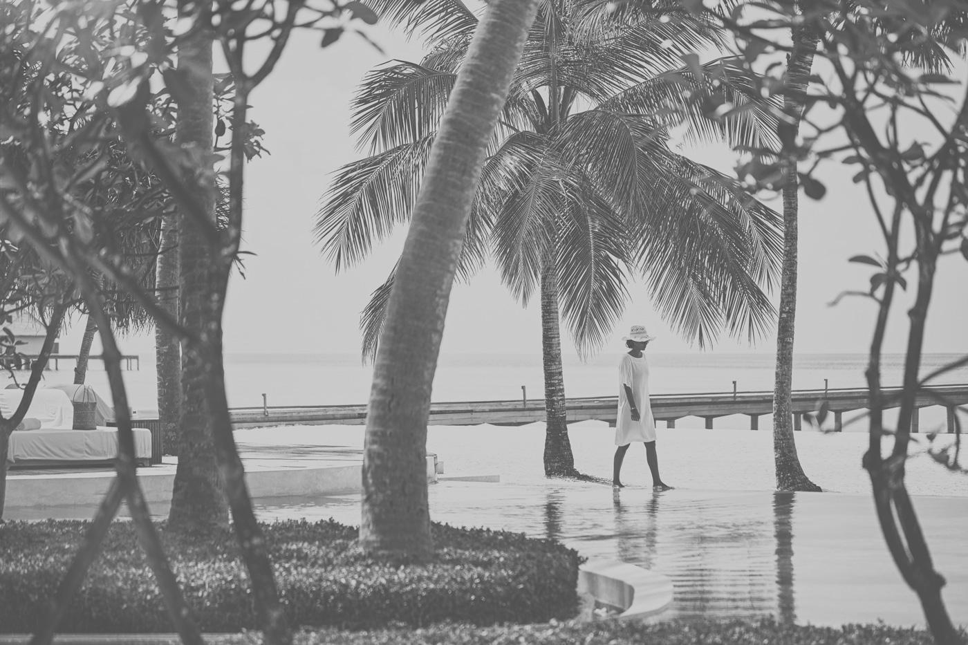 Frau spaziert neben einem Pool