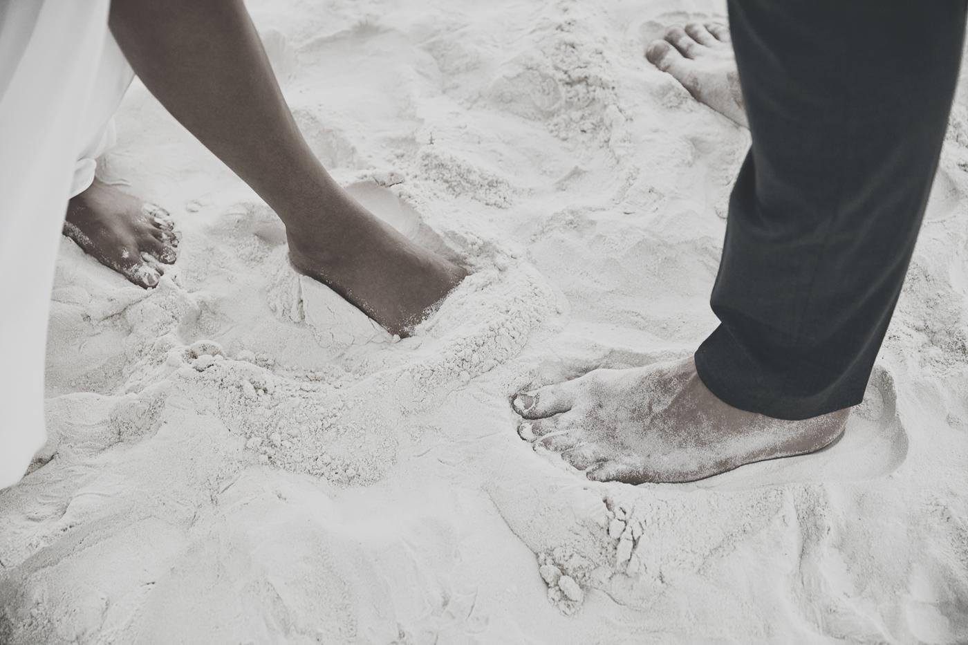 Hochzeitspaar steht Barfuß im Sand