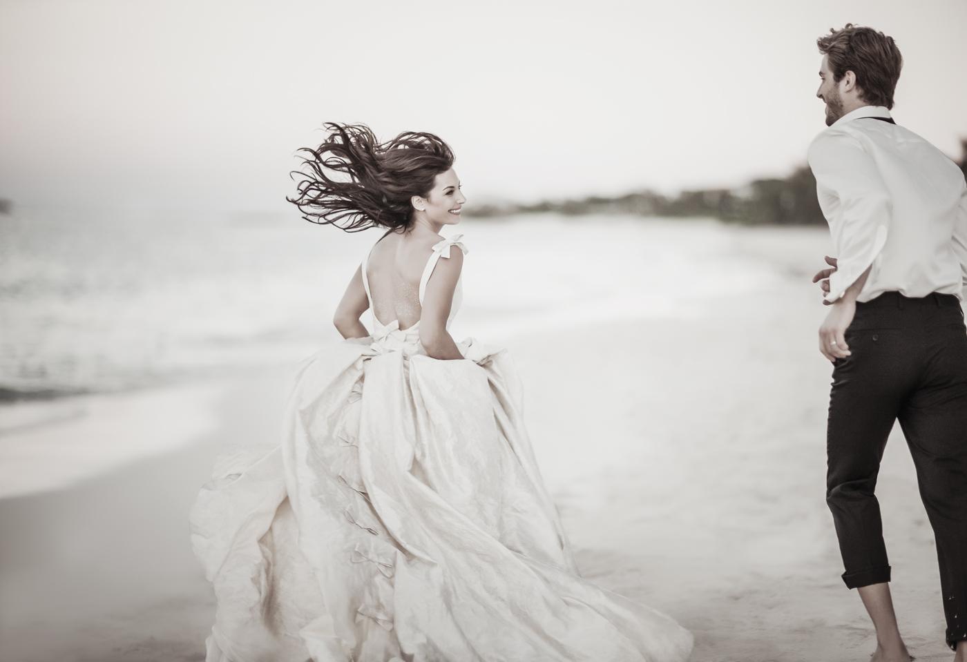 Braut und Bräutigam laufen über Strand im One&Only Reethi Rah