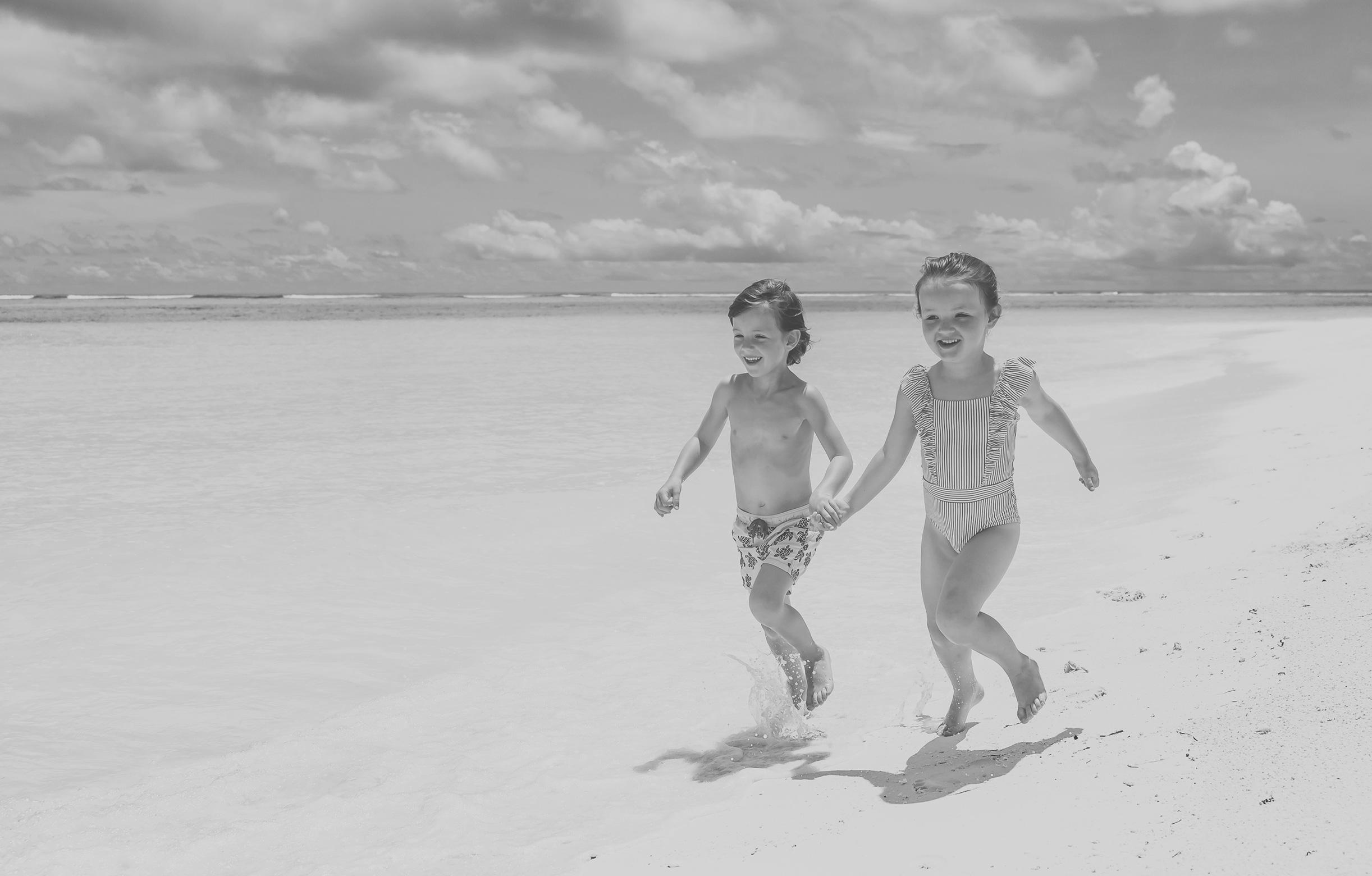 Kinder laufen über den Strand des Kanuhura