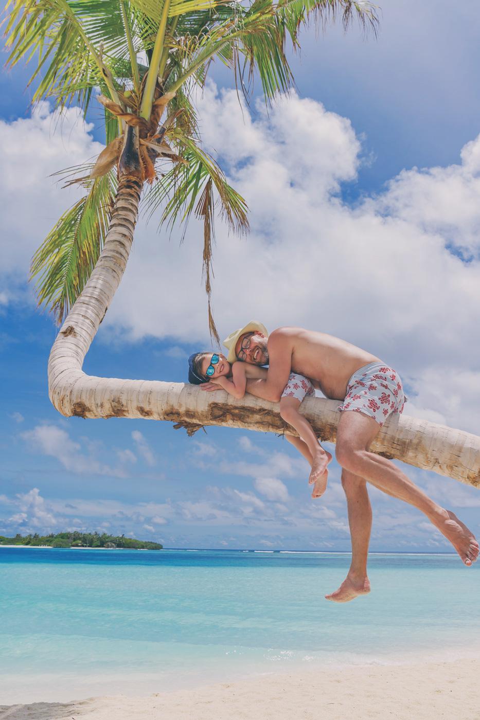Vater und Sohn liegen auf Palme am Strand des Kanuhura