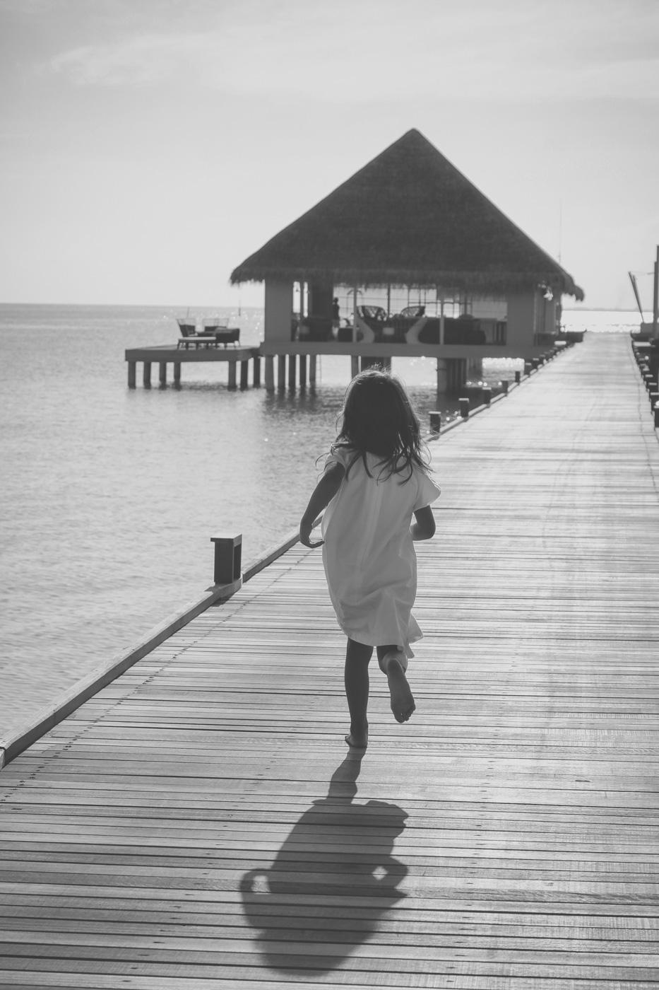 Kleines Mädchen läuft über den Steg des Kanuhura