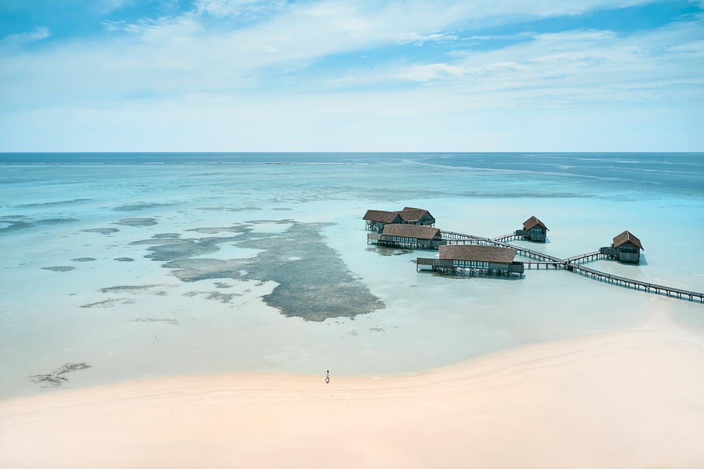 Frau spaziert über den Strand des COMO Cocoa Island