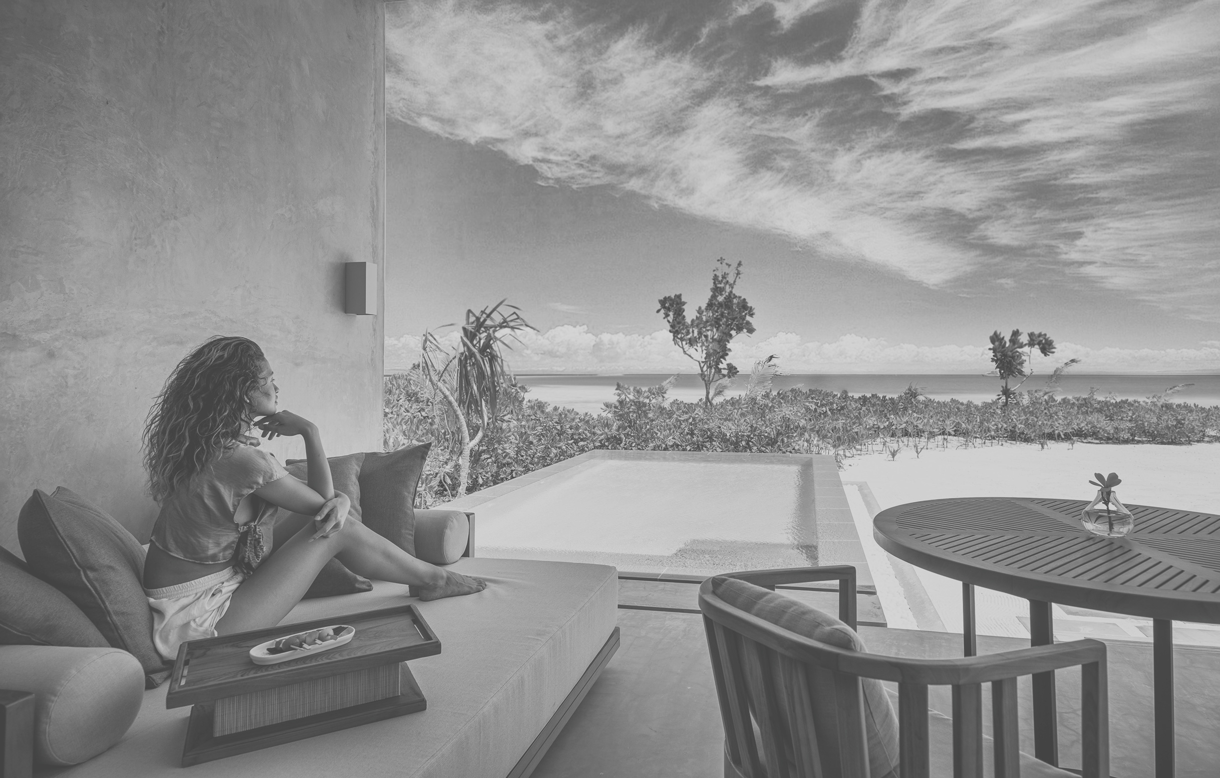 Frau entspannt auf Terrasse und Blickt auf das Meer