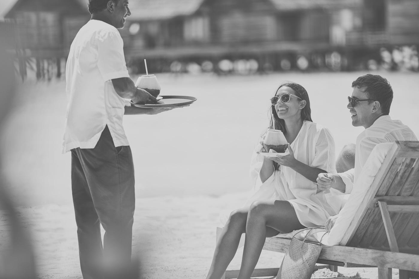 Pärchen trinkt Kokosnuss am Strand