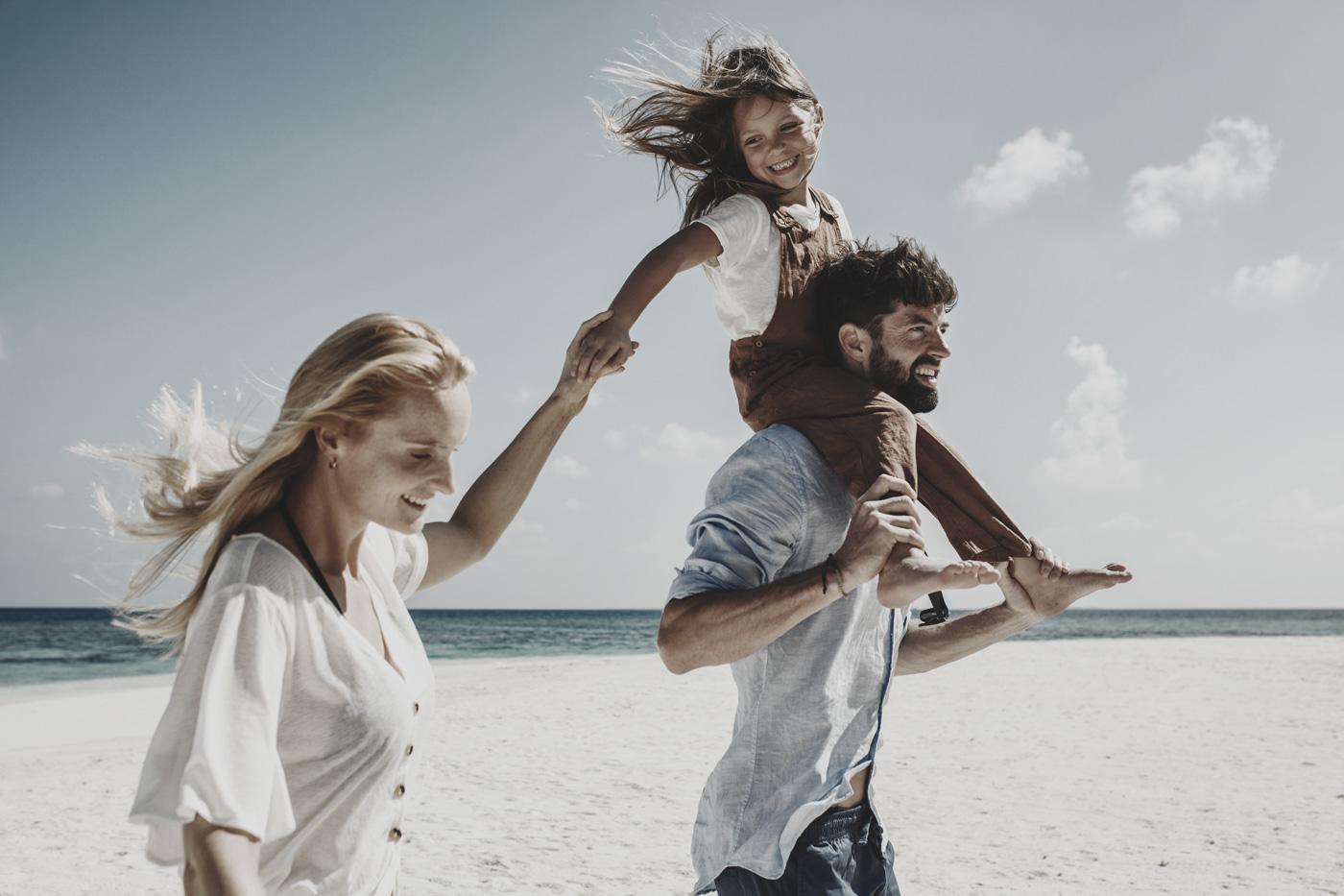 Familie spaziert über Malediven-Sandstrand