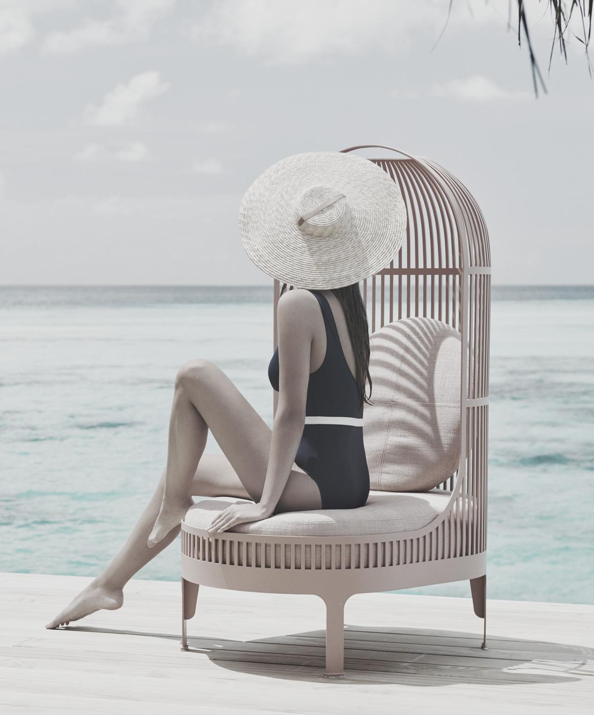 Frau sitzt auf Stuhl am Meer
