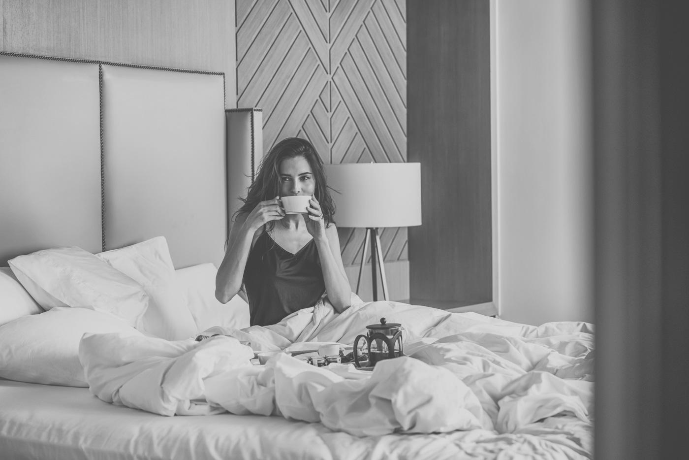 Frau frühstückt im Bett der Privatvilla im Waldorf Astoria