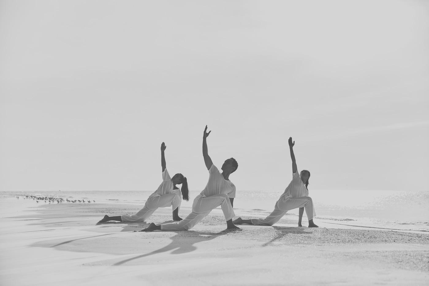 Menschen machen Yoga auf einer Sandbank