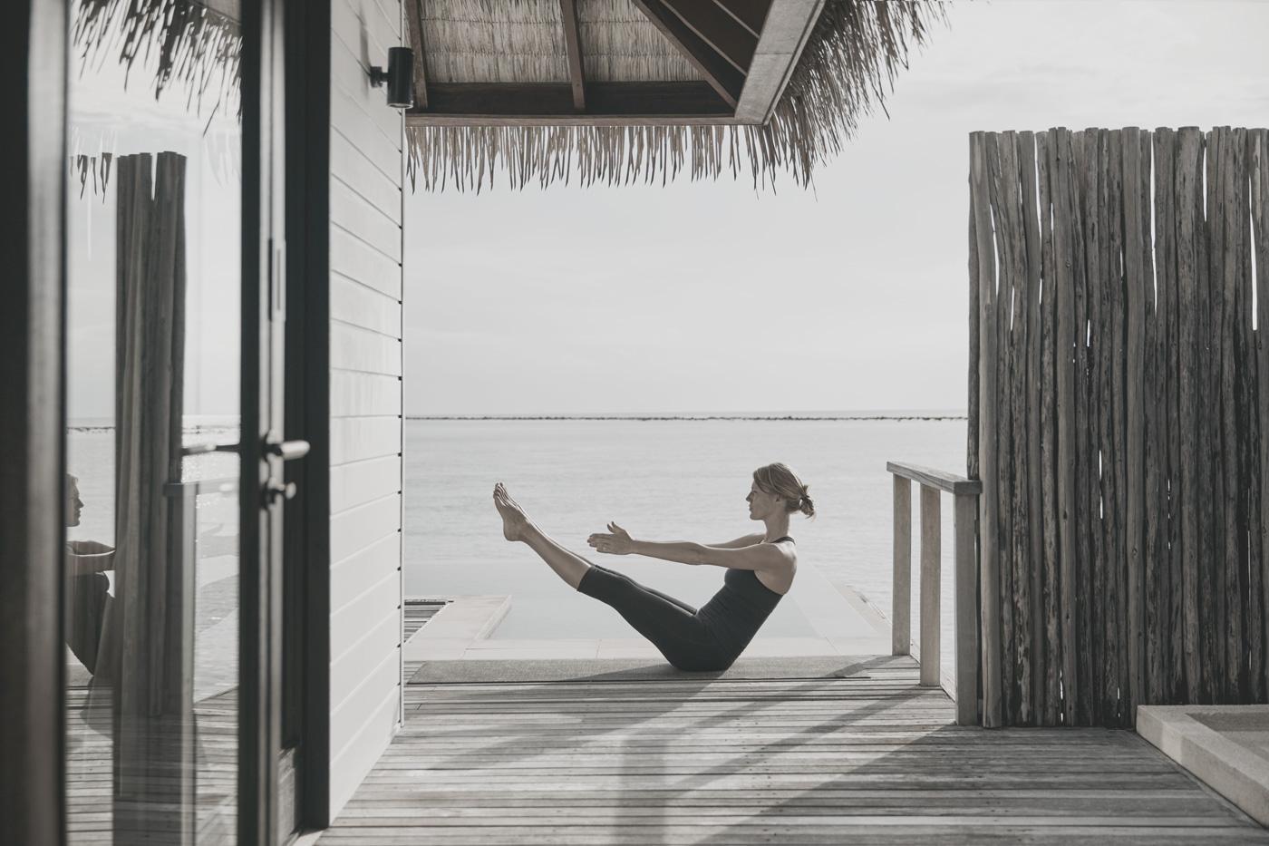 Frau macht Yoga auf Terasse einer Wasservilla im COMO Maalifushi