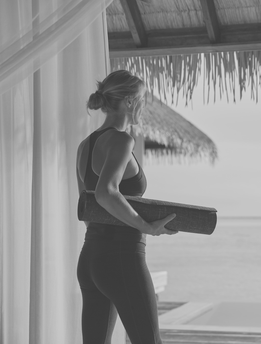 Frau mit Yogamatte in der Hand im COMO Maalifushi