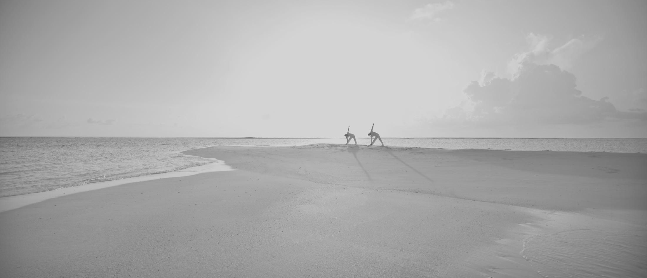Zwei Menschen machen Yoga auf einer Sandbank im Soneva Jani