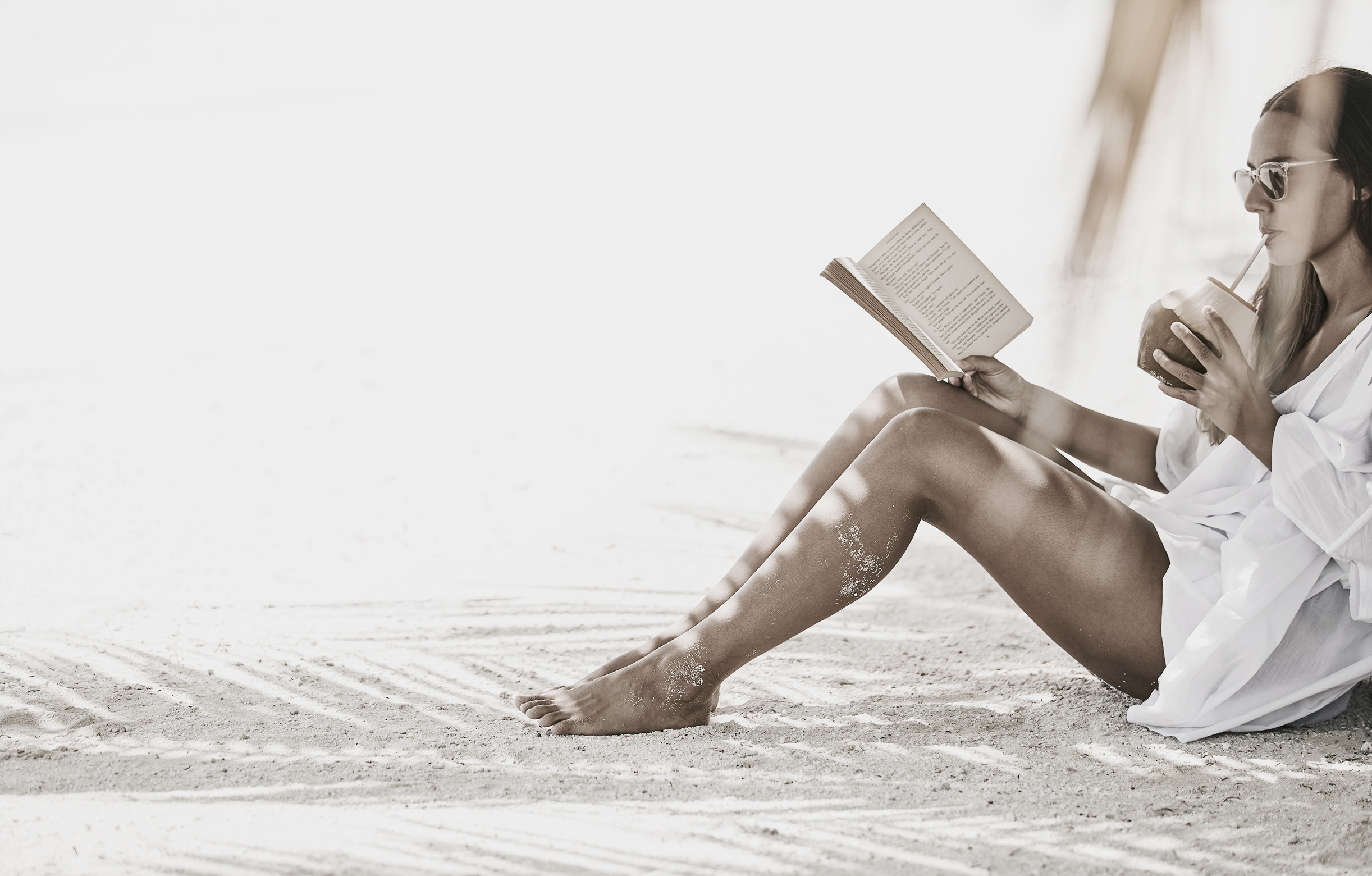 Frau liest ein Buch am Strand auf den Malediven