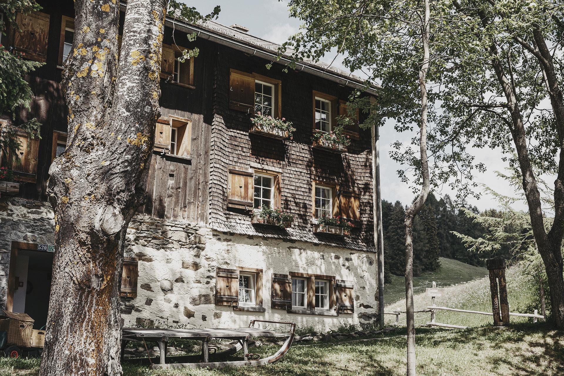 Außenansicht einer Hütte im Almdorf Guarda Val Lenzerheide –