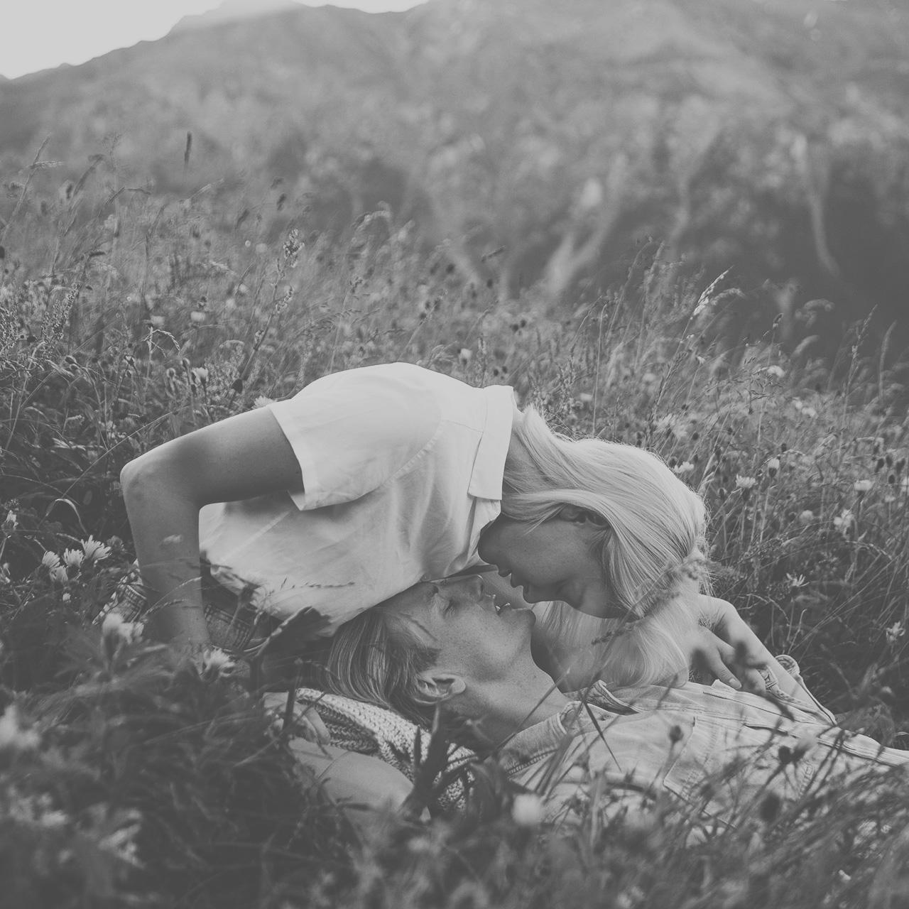 Pärchen küsst sich in einer Almwiese des Guarda Val