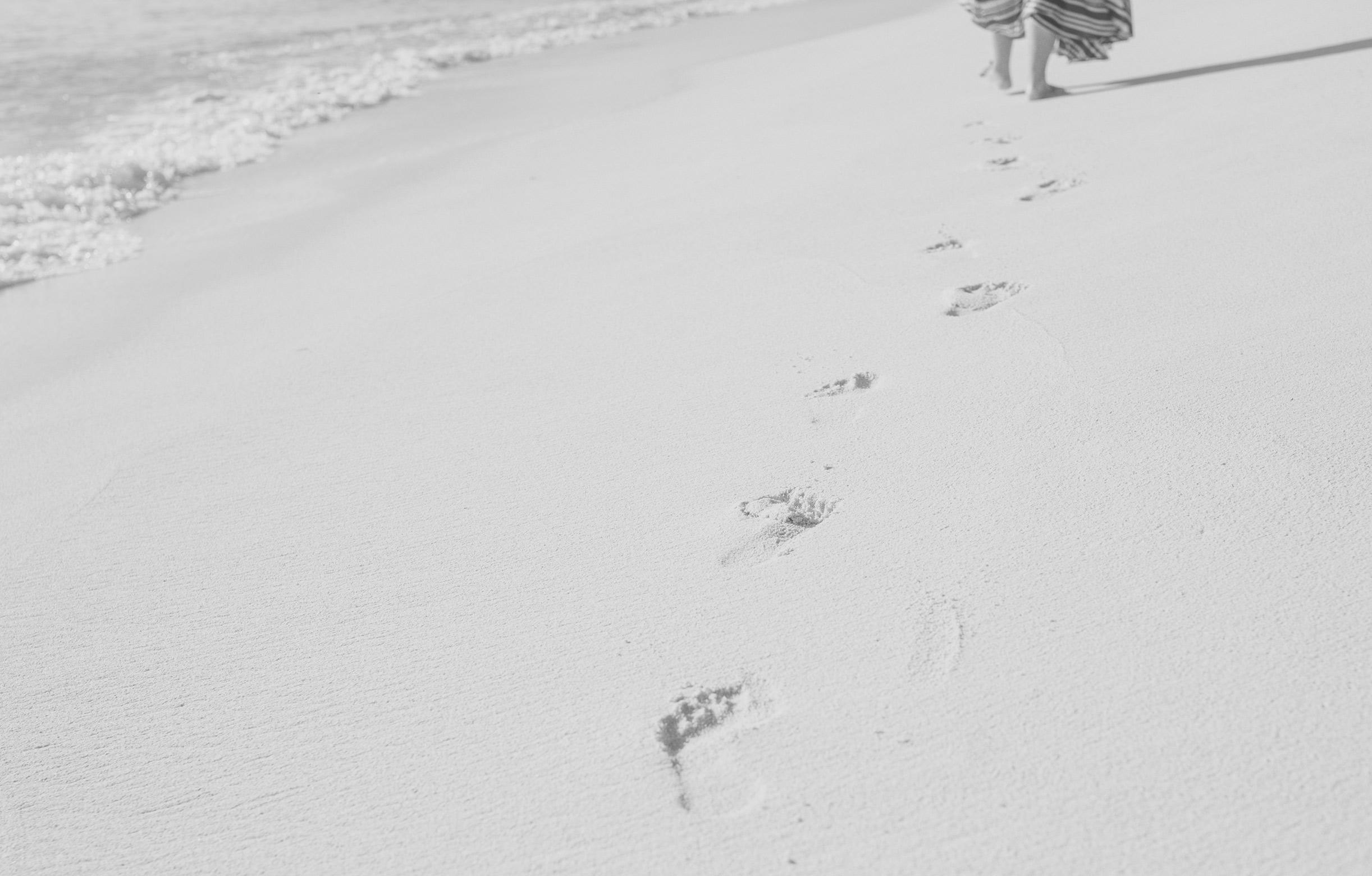 Fussspuren entlang eines Strandes