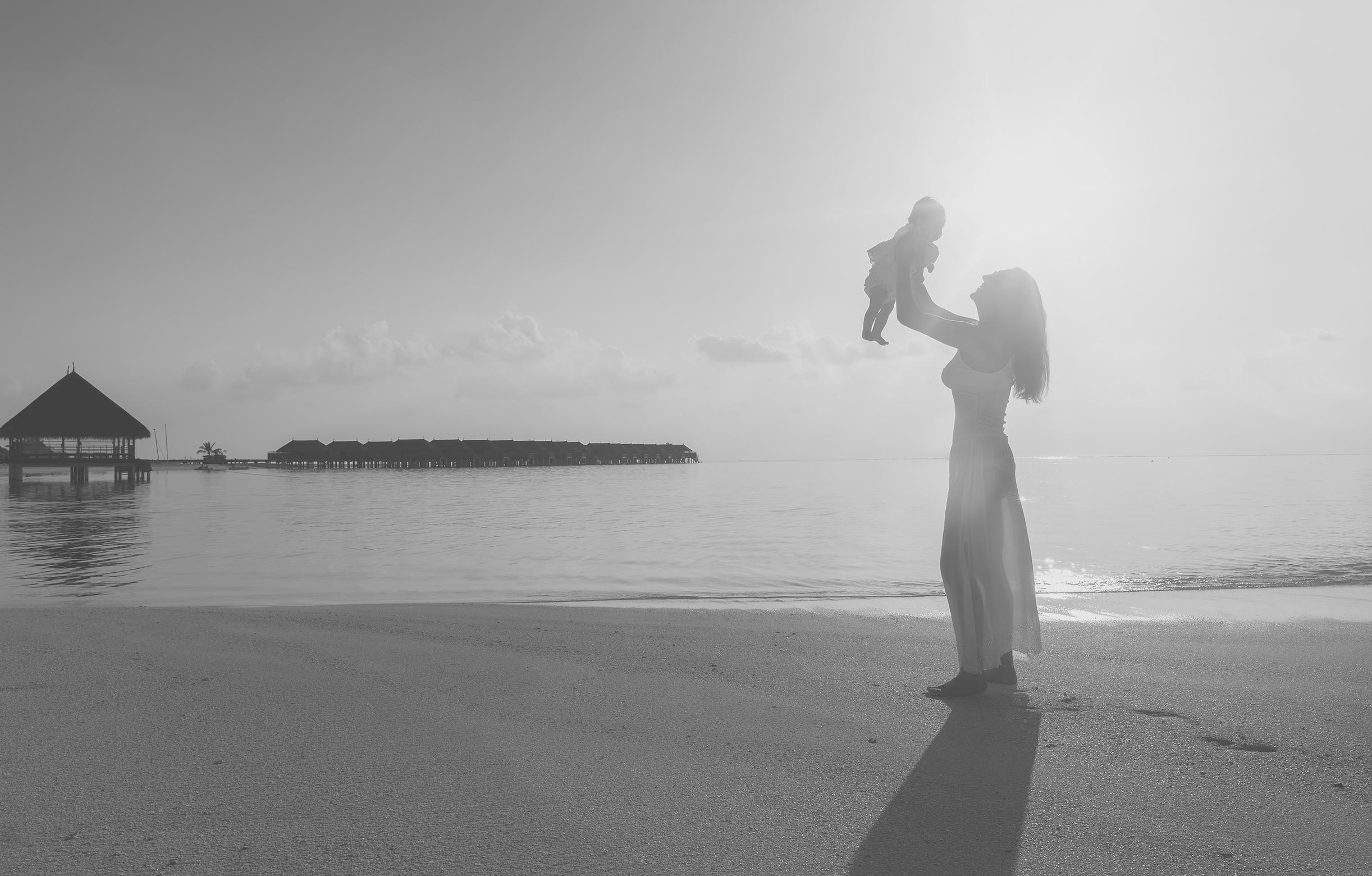 Frau am Strand hält Baby hoch